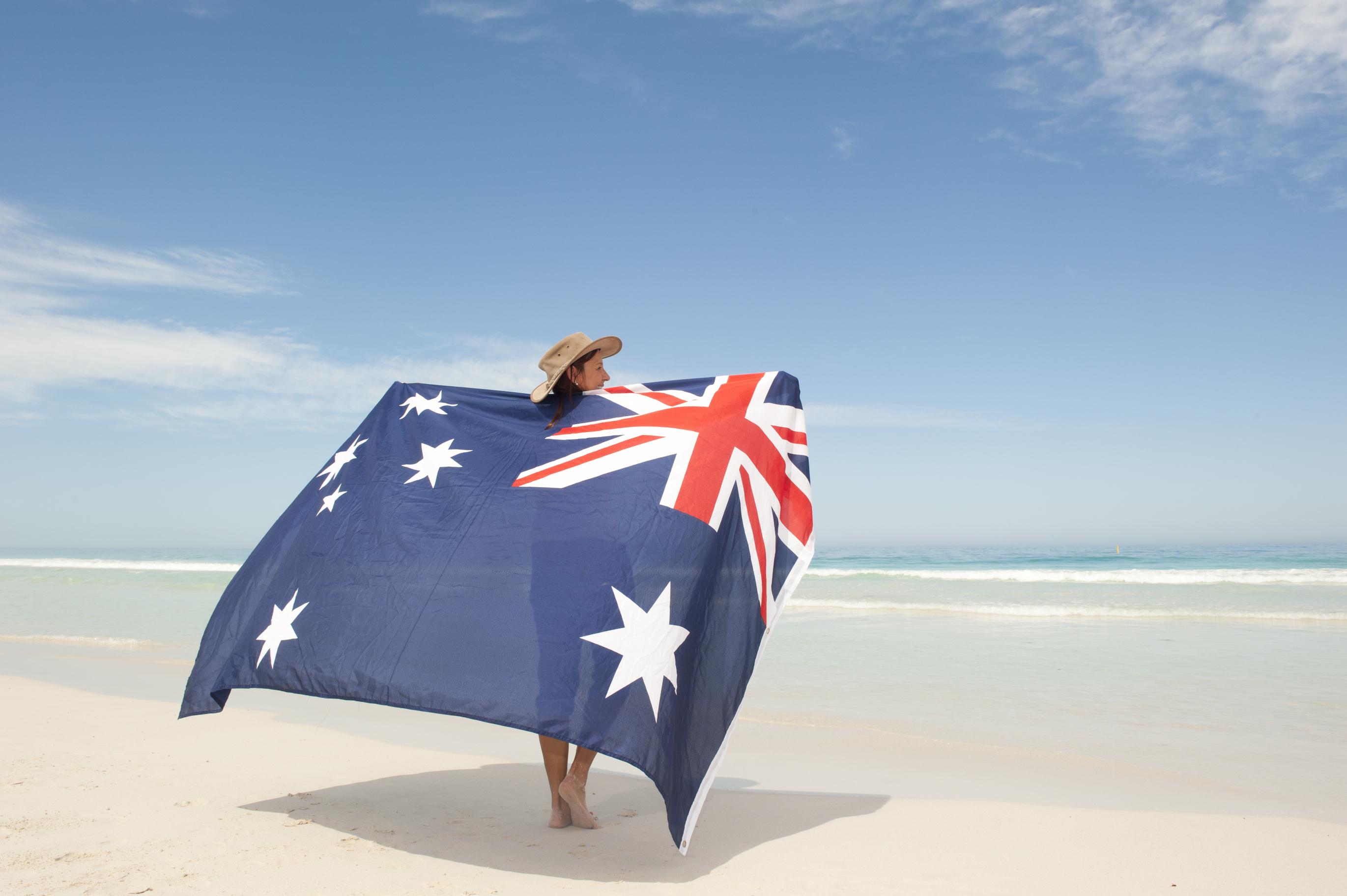 Woman holding the Australian flag on the beach.