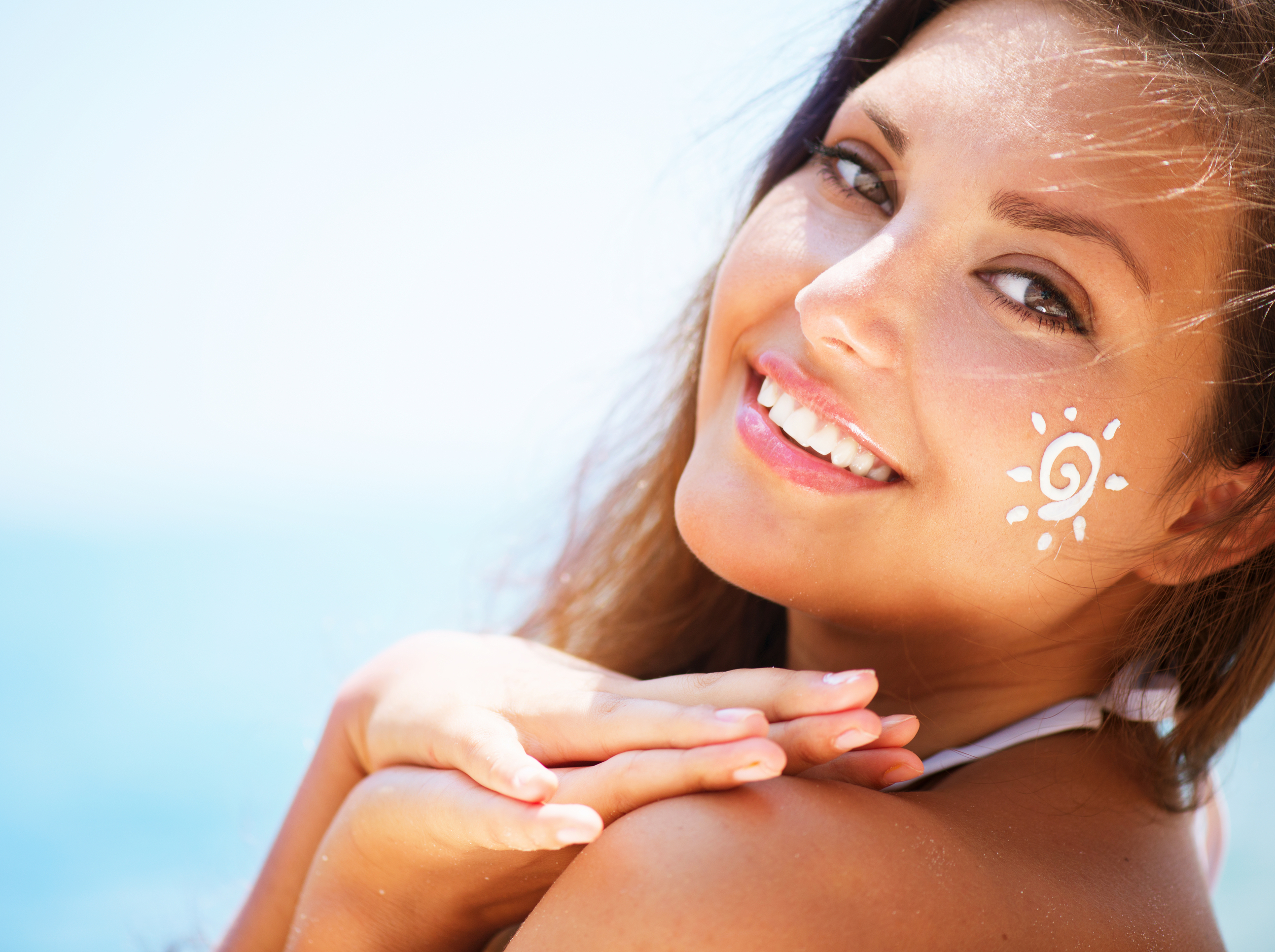 Happy woman with a sun made of sun cream on her face.
