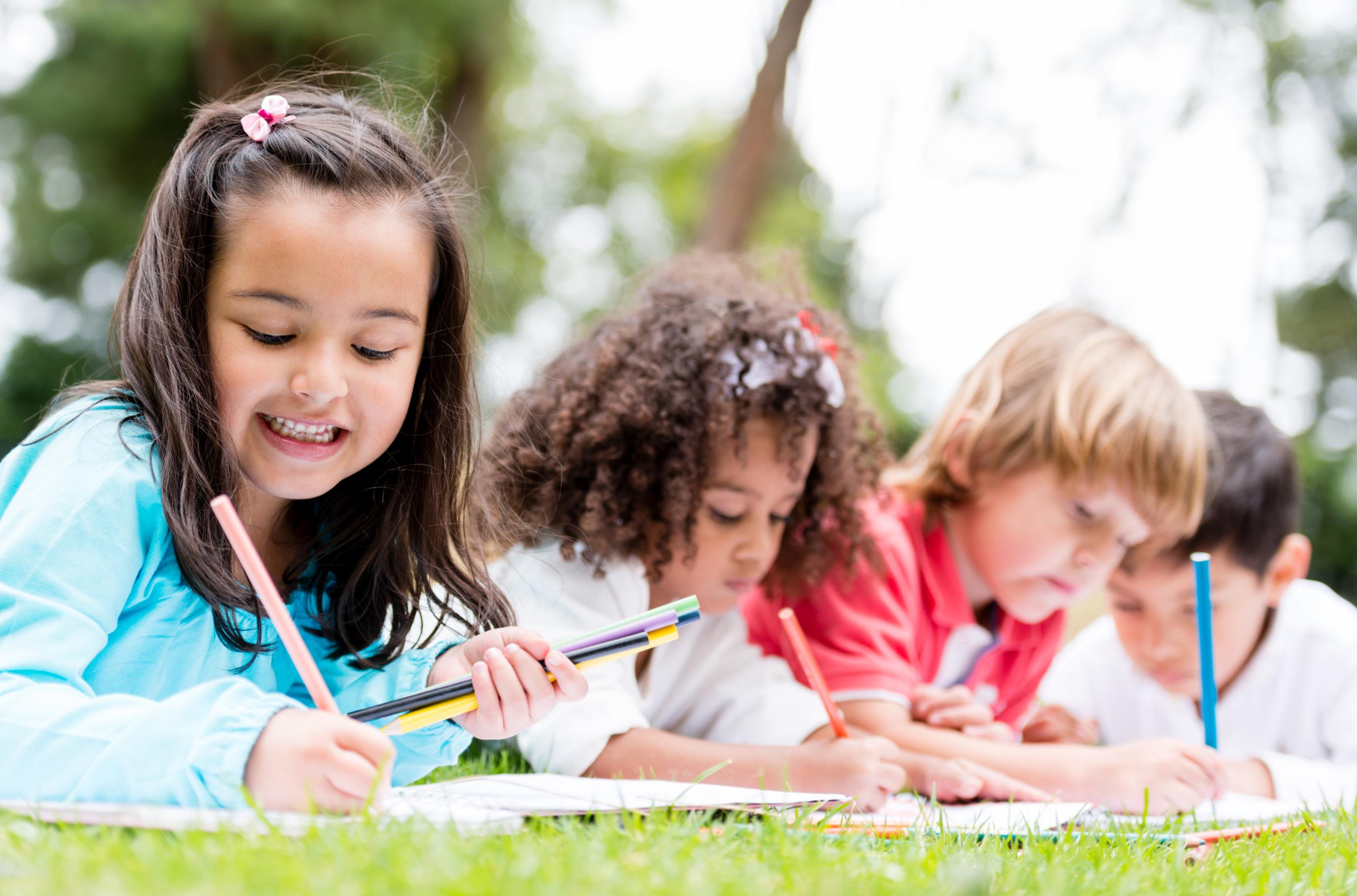 School kids having fun on the grass painting on books.