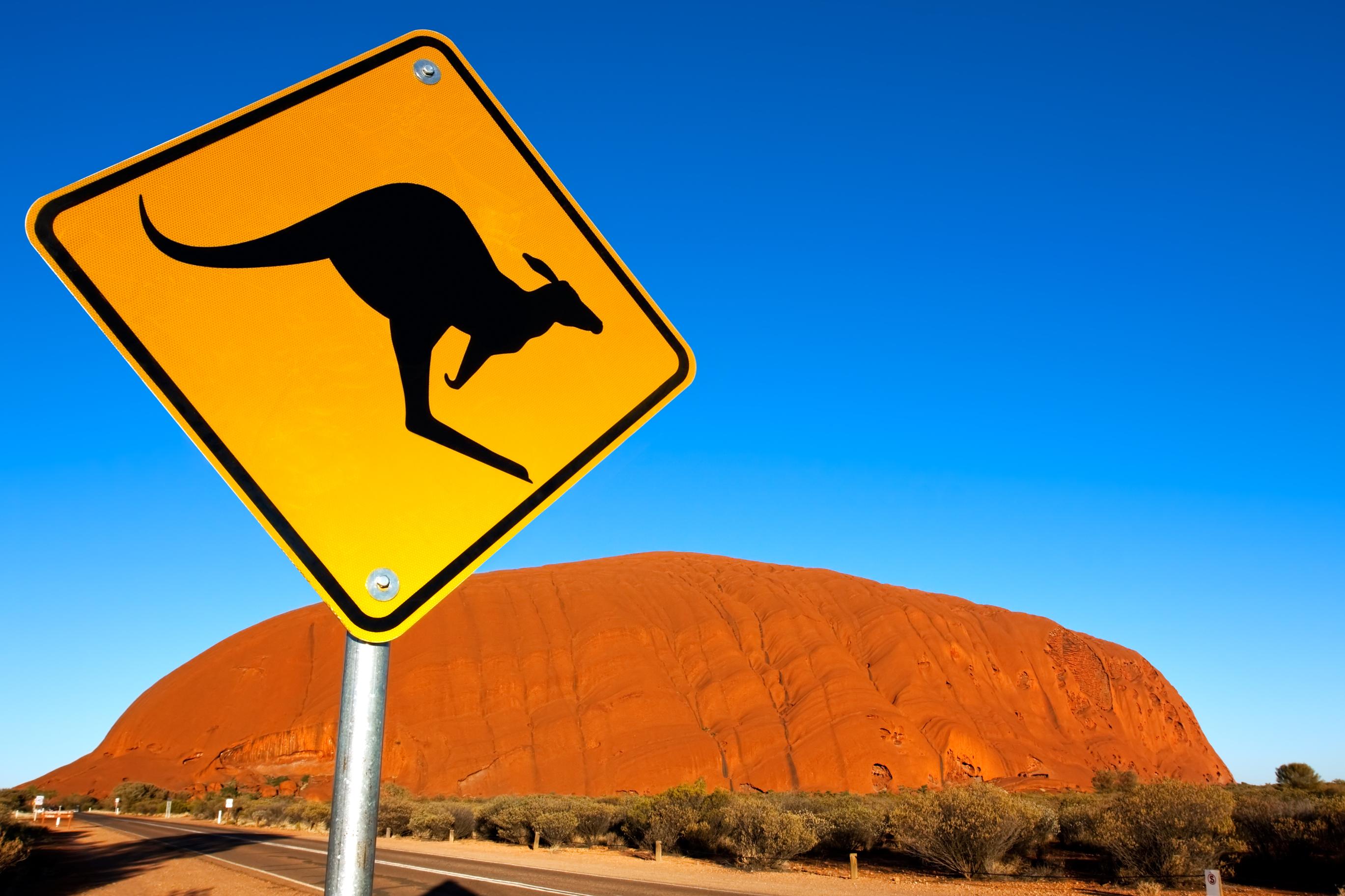 Kangaroo sign with Uluru in the background.