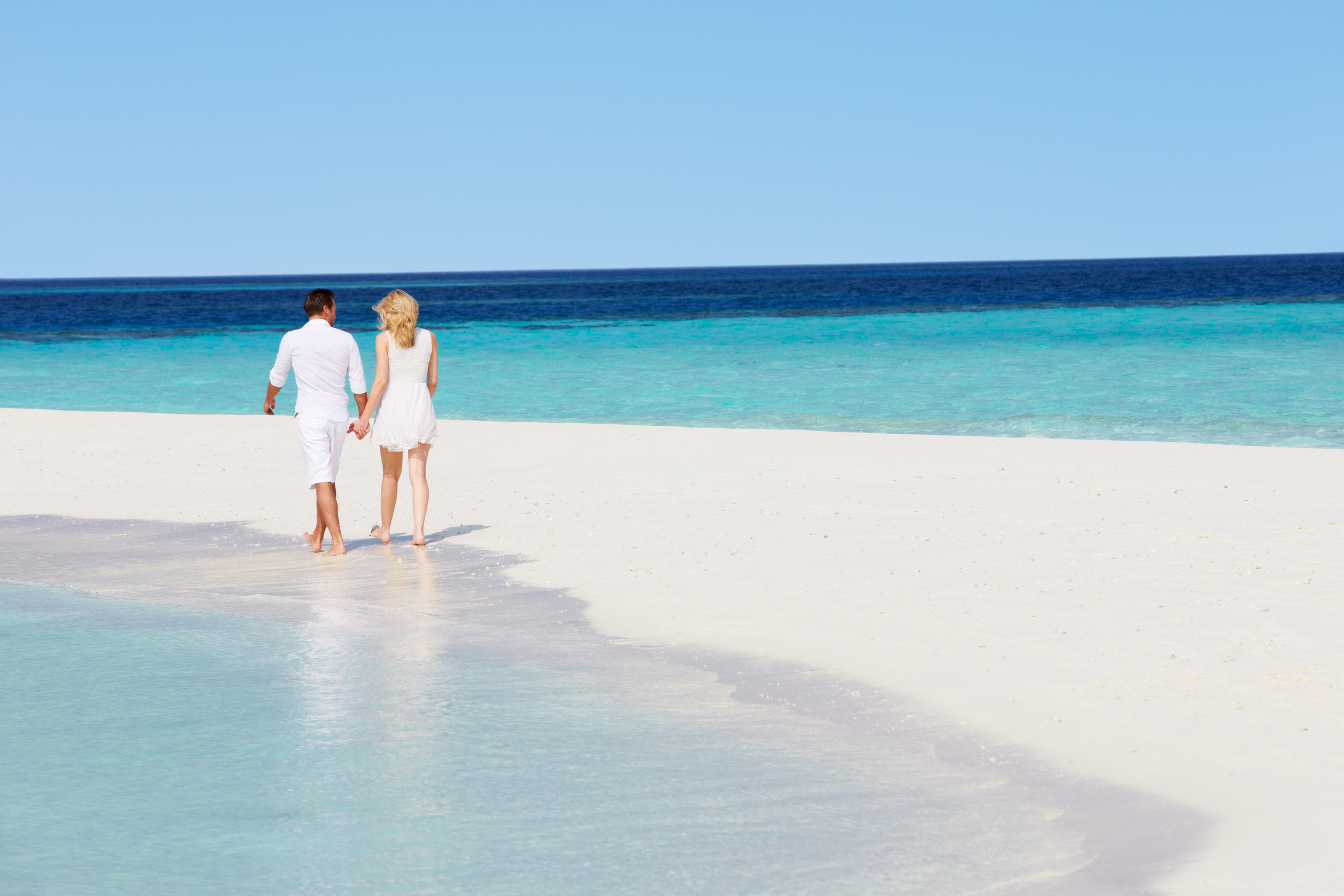Romantic couple holding hands and walking down the beach.