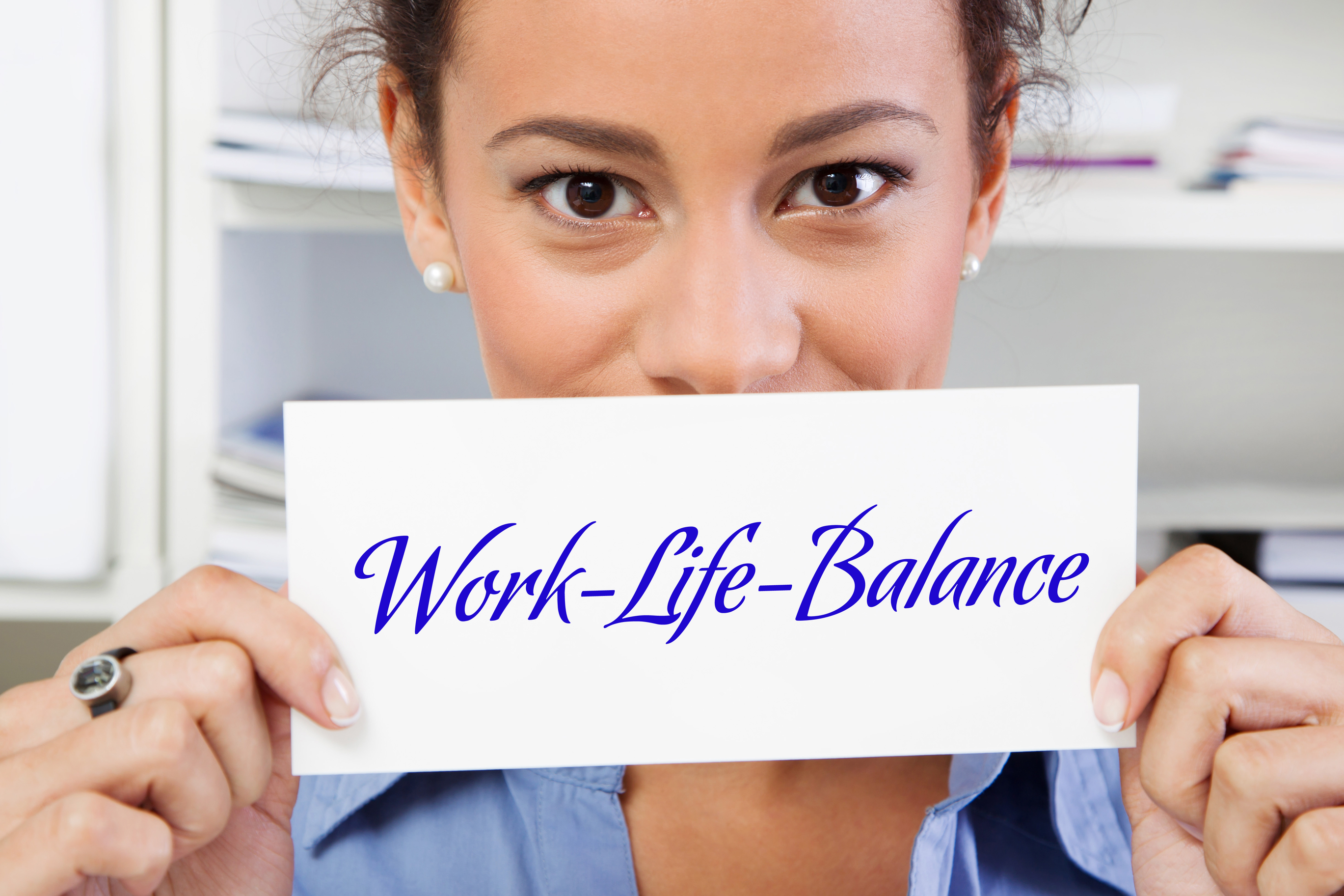 Woman holding a work life balance paper sign