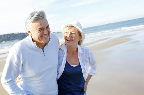 Elderly couple walking down the beach.