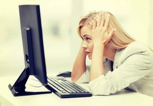 Woman stressed looking at a computers screen