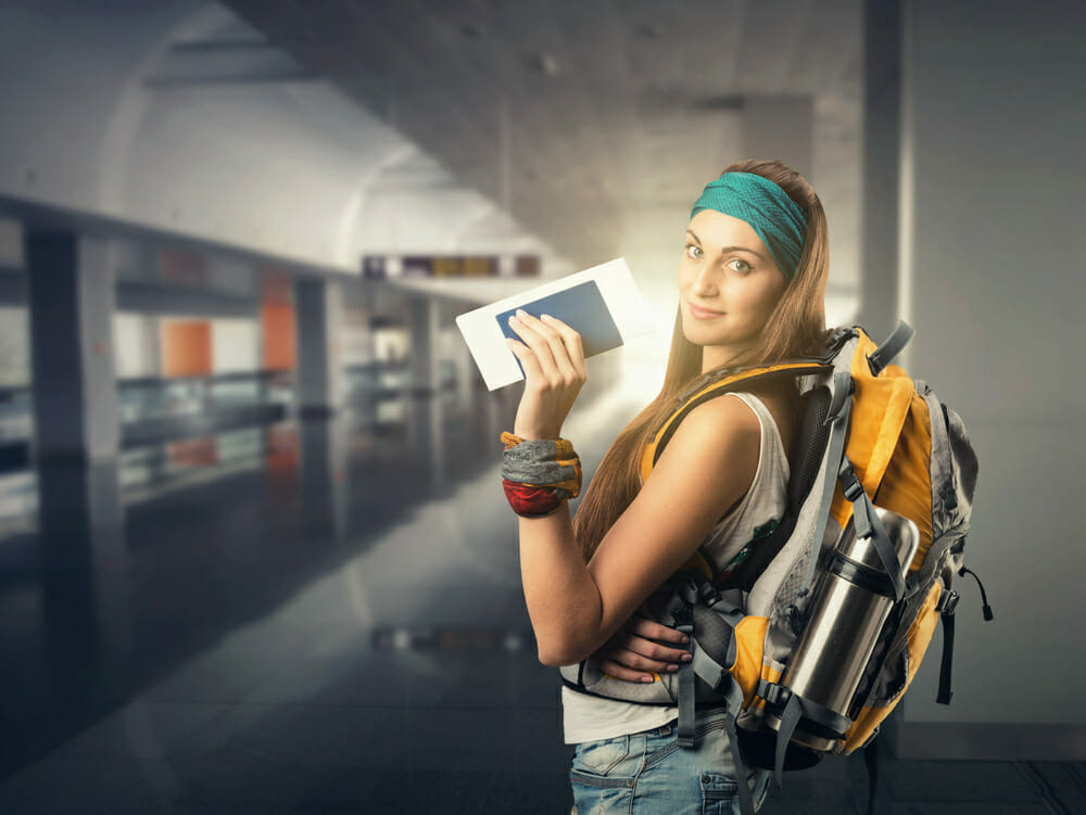 Backpacker at train station holding passport and 408 visa