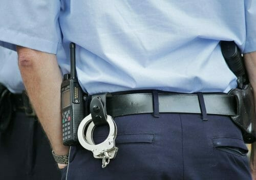 Close-up of police officer's belt from behind, showing radio and handcuffs