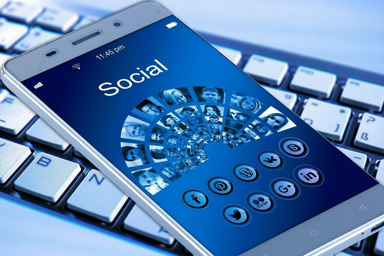 Blue phone with social media icons in front of a keyboard