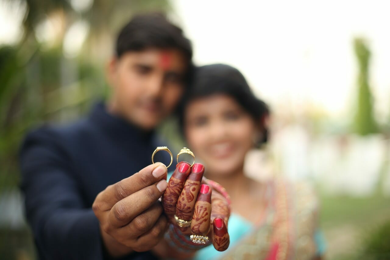 Close-up of couple holding wedding rings up
